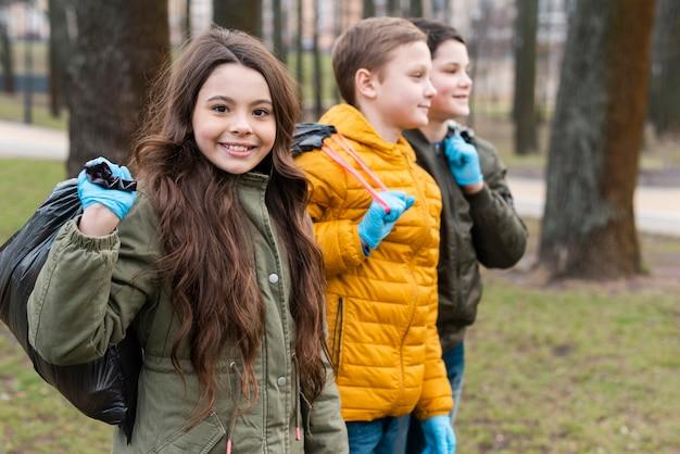 Vooraanzicht van lachende kinderen dragen plastic zakken