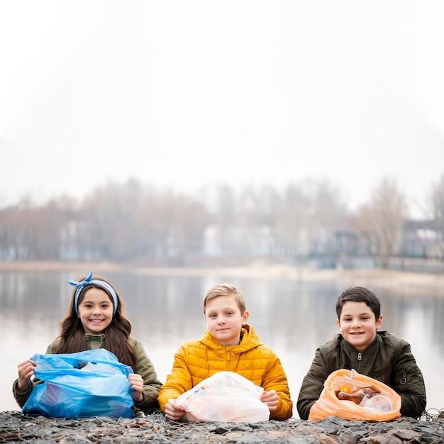 Vooraanzicht van lachende kinderen met plastic zakken
