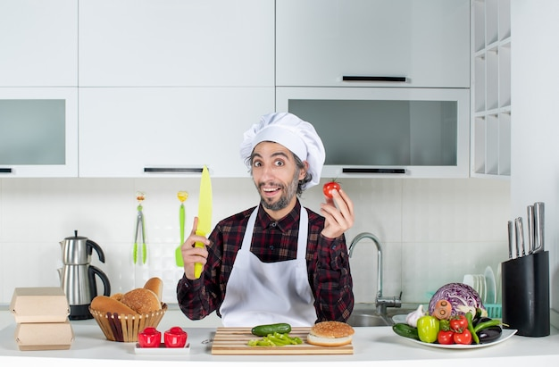 Vooraanzicht van lachende mannelijke chef-kok met tomaat en mes in de keuken