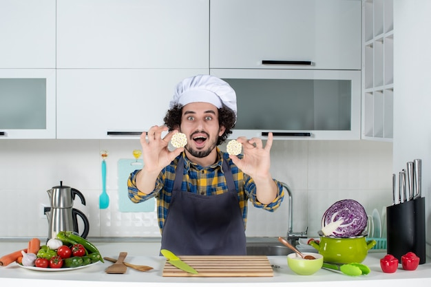 Vooraanzicht van lachende mannelijke chef-kok met verse groenten en koken met keukengerei en het eten in de witte keuken tonen