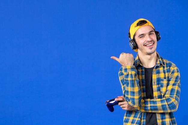 Vooraanzicht van lachende mannelijke gamer met gamepad op een blauwe muur