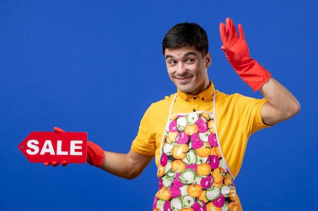Vooraanzicht van lachende mannelijke huishoudster in geel t-shirt en schort met verkoopbord op blauwe muur