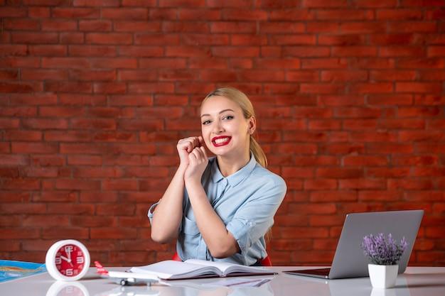 Vooraanzicht van lachende reisagent zit achter haar werkplek toerisme bezetting globale service kaartservice binnenshuis bureau manager assistent