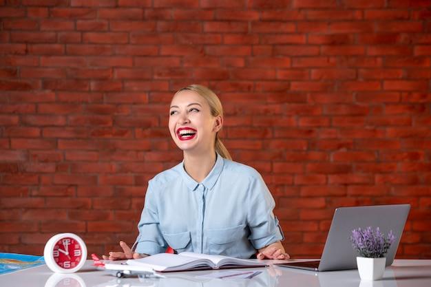Vooraanzicht van lachende reisagent zit achter haar werkplek toerisme manager bezetting assistent kaart global agency service binnenshuis