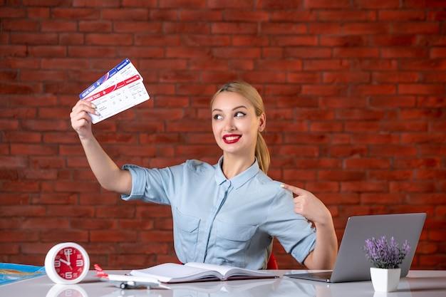 Vooraanzicht van lachende reisagent zittend achter haar werkplek met vliegtickets global manager agency binnenshuis service assistent toerisme vlucht bezetting kaart