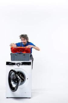 Vooraanzicht van lachende reparateur die gereedschapstas opent achter wasmachine op witte muur
