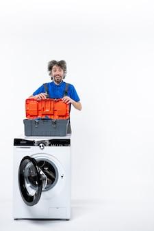 Vooraanzicht van lachende reparateur met gereedschapstas achter wasmachine op witte muur