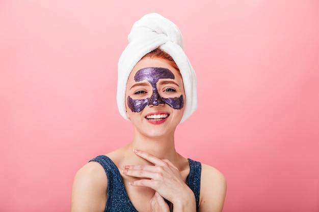 Vooraanzicht van lachende vrouw in handdoek en masker geïsoleerd op roze achtergrond. gelukkig meisje dat gezichtstreament met glimlach doet.