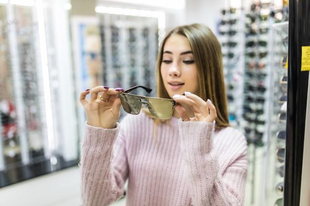 Vooraanzicht van lachende vrouw in witte trui probeer glazen in professionele winkel op