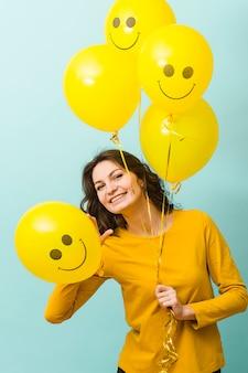 Vooraanzicht van lachende vrouw met ballonnen