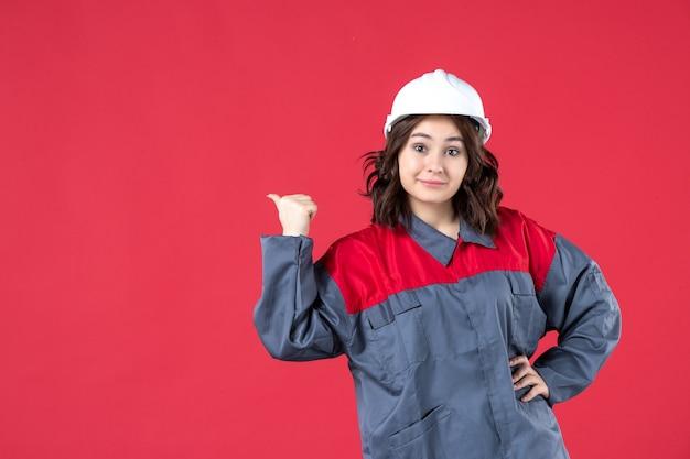 Vooraanzicht van lachende vrouwelijke bouwer in uniform met harde hoed en ok gebaar maken op geïsoleerde rode achtergrond
