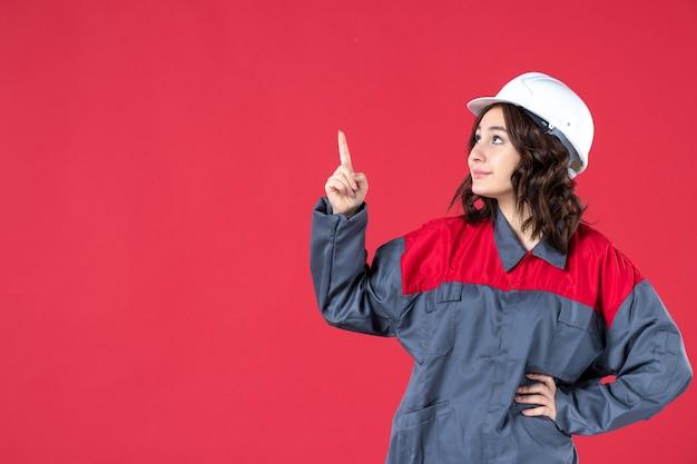 Vooraanzicht van lachende vrouwelijke bouwer in uniform met harde hoed en omhoog wijzend op geïsoleerde rode achtergrond