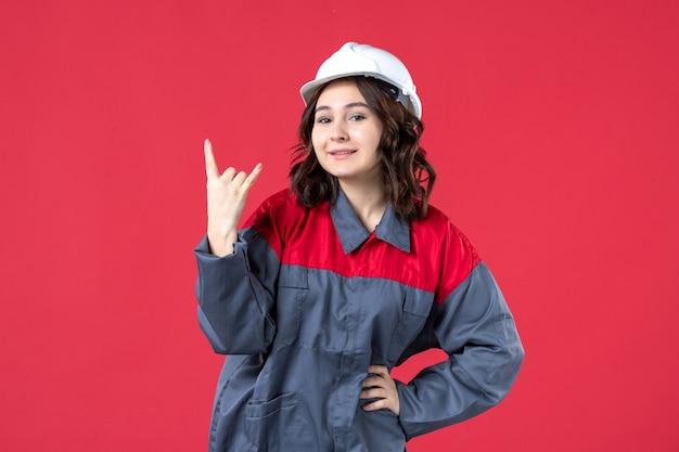 Vooraanzicht van lachende vrouwelijke bouwer in uniform met harde hoed en overwinningsgebaar maken op geïsoleerde rode achtergrond
