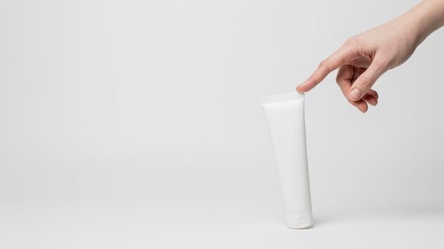 Vooraanzicht van lege cosmetische productverpakking in de hand
