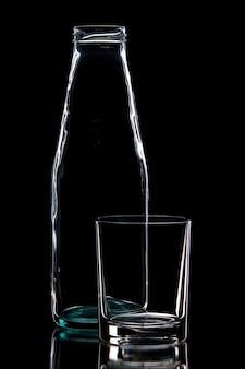 Vooraanzicht van lege fles en een glas op zwarte achtergrond met vrije ruimte