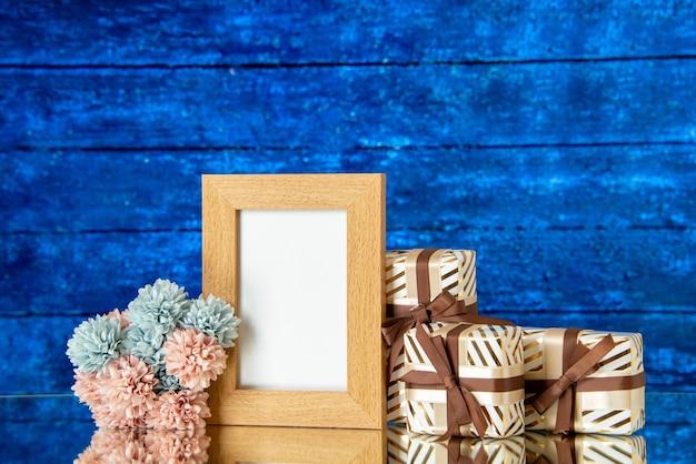 Vooraanzicht van lege fotolijst vakantie presenteert bloemen op blauwe achtergrond