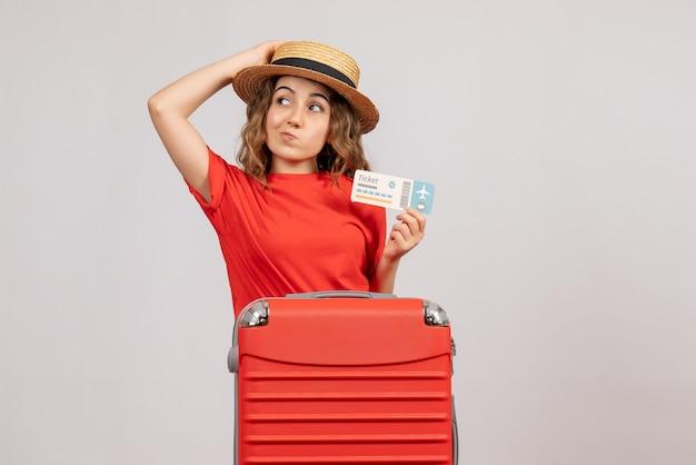 Vooraanzicht van leuk vakantiemeisje met haar valise holding kaartje