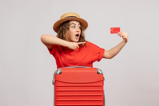 Vooraanzicht van leuk vakantiemeisje met haar valise holdingskaart