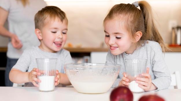 Vooraanzicht van leuke broers en zussen die thuis koken