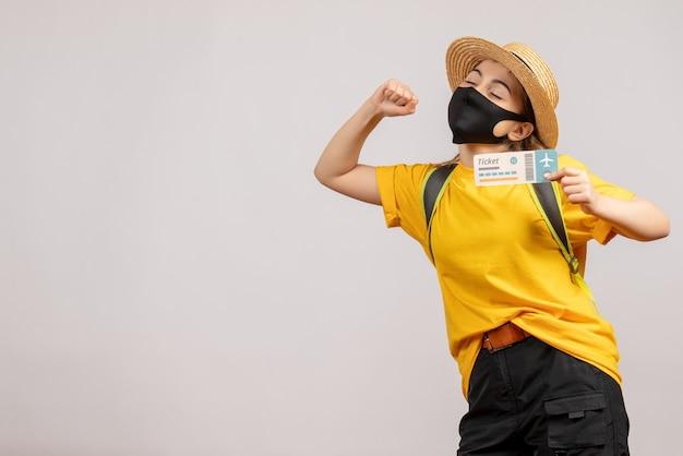 Vooraanzicht van leuke vrouwelijke reiziger met rugzak die het zwarte reisticket van de maskerholding op witte muur dragen