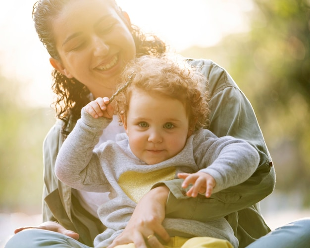 Vooraanzicht van lgbt-moeder buiten in het park met haar kind