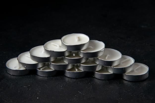 Vooraanzicht van lichte kaarsen in kleine metalen blikjes op zwart