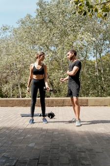 Vooraanzicht van man en vrouw buitenshuis die samen voorbereiden om uit te oefenen