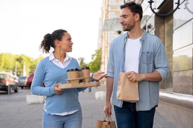 Vooraanzicht van man en vrouw buitenshuis met afhaalmaaltijden
