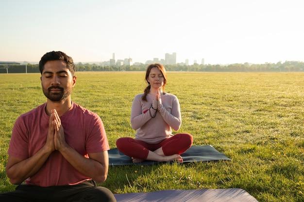 Vooraanzicht van man en vrouw die buiten mediteren op yogamatten