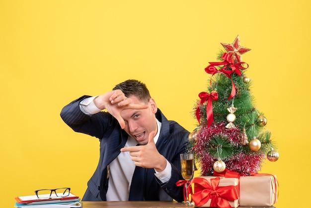 Vooraanzicht van man in pak camera teken zittend aan de tafel in de buurt van kerstboom en geschenken op geel maken