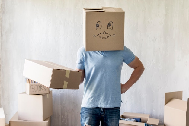 Vooraanzicht van man met doos boven hoofd poseren tijdens het inpakken om te verplaatsen