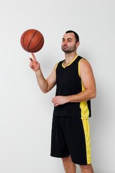 Vooraanzicht van mannelijk speler in evenwicht brengend basketbal op één vinger