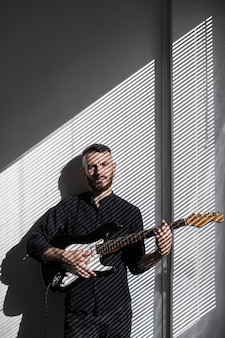 Vooraanzicht van mannelijke artiest elektrische gitaar spelen naast venster