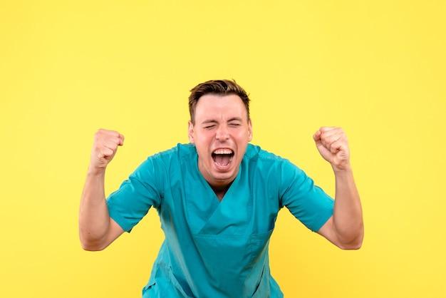 Vooraanzicht van mannelijke arts die emotioneel op gele muur verheugt