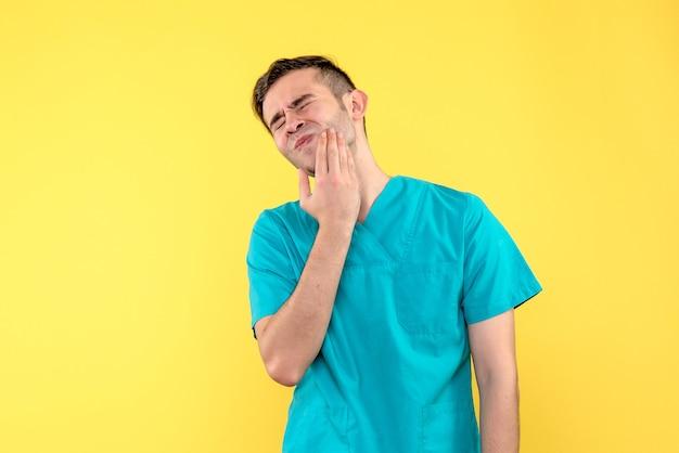 Vooraanzicht van mannelijke arts die kiespijn op gele muur heeft