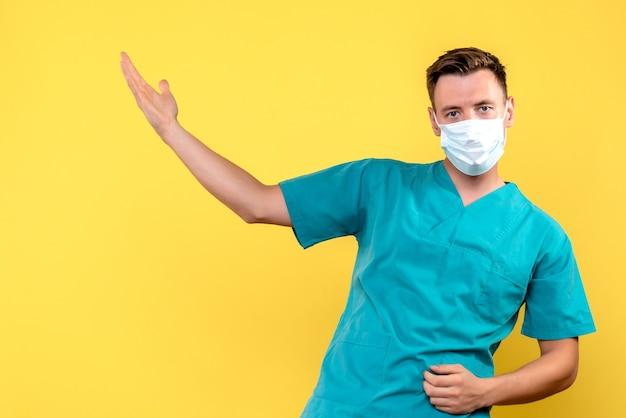 Vooraanzicht van mannelijke arts die masker op gele muur draagt