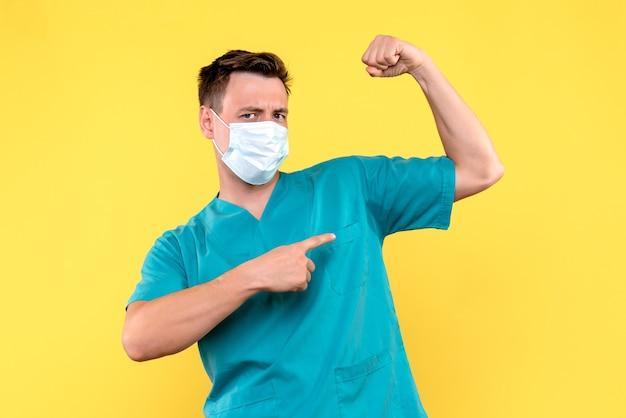 Vooraanzicht van mannelijke arts die met masker op gele muur buigt