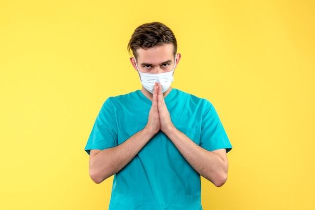 Vooraanzicht van mannelijke arts die op gele muur bidt