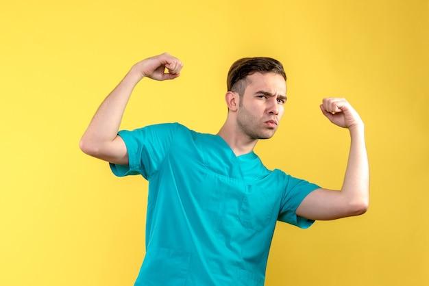 Vooraanzicht van mannelijke arts die op gele muur buigt