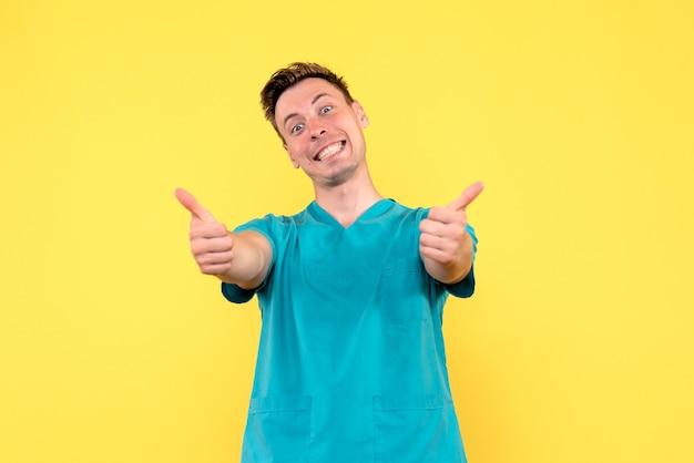 Vooraanzicht van mannelijke arts die op gele muur glimlacht