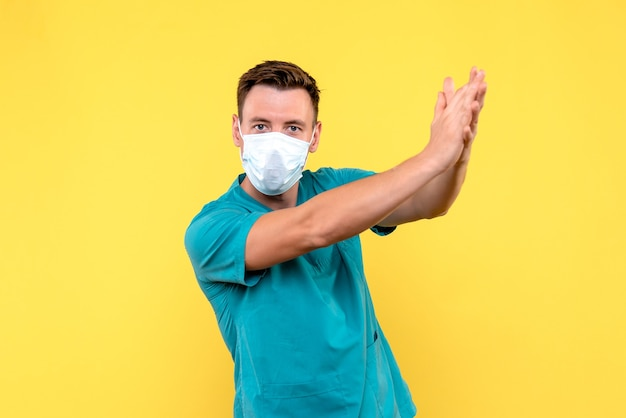 Vooraanzicht van mannelijke arts die op gele muur klapt