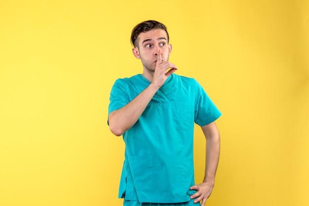 Vooraanzicht van mannelijke arts die op gele muur stil vraagt
