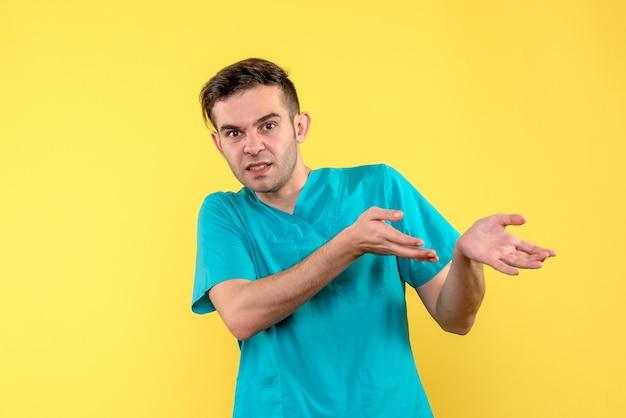 Vooraanzicht van mannelijke arts die op gele muur wordt verward