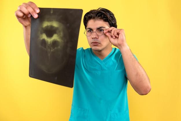 Vooraanzicht van mannelijke arts die röntgenfoto vasthoudt
