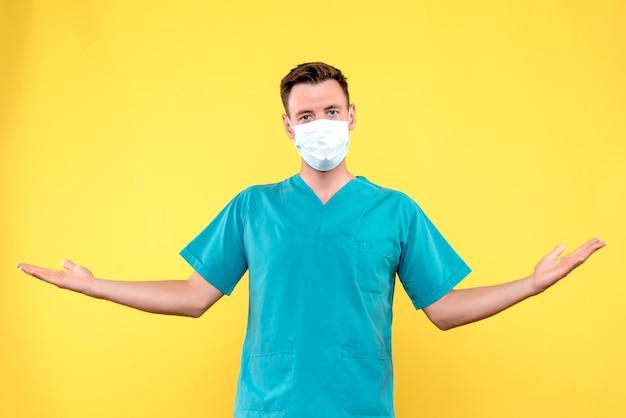 Vooraanzicht van mannelijke arts die zich gewoon op gele muur bevindt