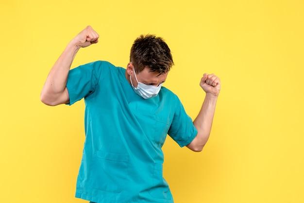 Vooraanzicht van mannelijke arts die zich met masker op gele muur verheugt