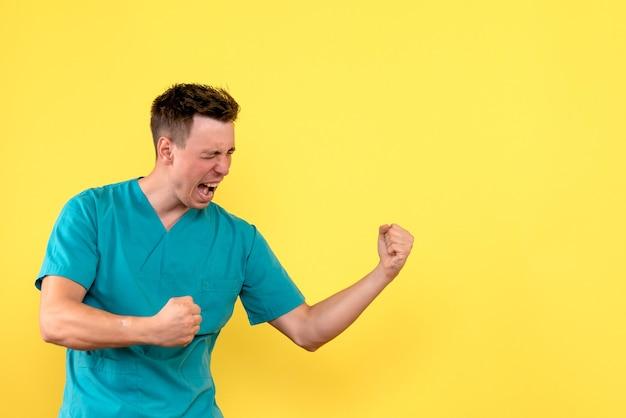 Vooraanzicht van mannelijke arts die zich op gele muur verheugt