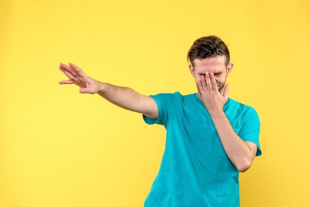 Vooraanzicht van mannelijke arts die zijn gezicht op gele muur behandelt