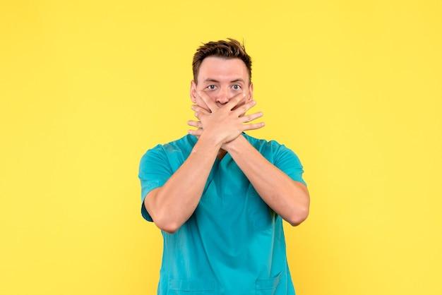 Vooraanzicht van mannelijke arts die zijn mond op gele muur behandelt