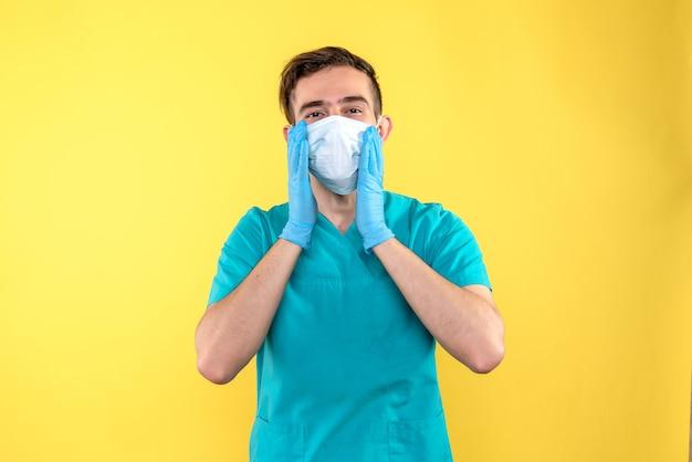 Vooraanzicht van mannelijke arts in handschoenen en masker op gele muur